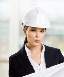 Female engineer in white hard hat hands blueprint. Concept of successful construction